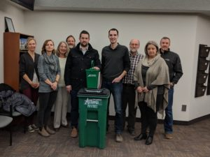 "A group of nine people stand around a large green bin on wheels, which says ""Altogether Altona"". On top of this bin is a smaller green pail which reads ""Access Credit Union""."