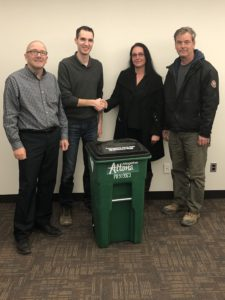 Four people stand with a large green compost bin which says Altogether Altona. Two of the people, a man and a woman, are shaking hands above the bin.